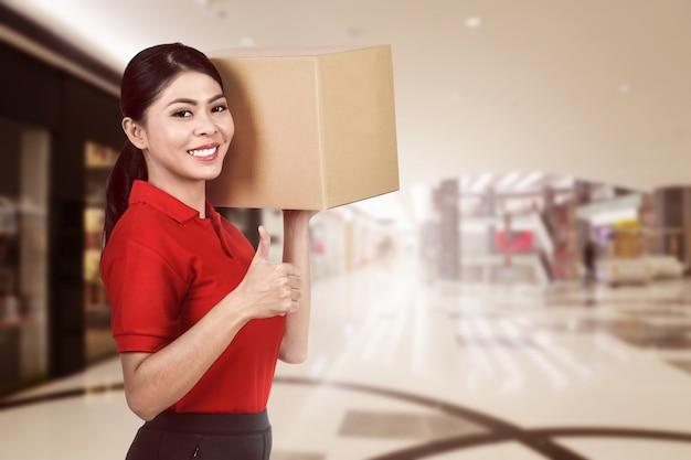 Lächelnde asiatische kurierfrau, die das paket trägt