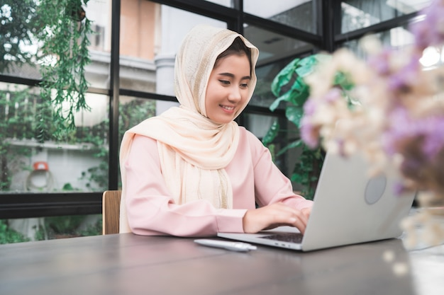 Lächelnde asiatische moslemische frau der schönen junge, die an dem laptop zu hause sitzt im wohnzimmer arbeitet