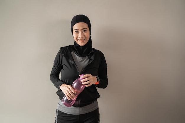 Lächelnde asiatische muslimische frauen, die hijab-sportbekleidung tragen, halten eine flasche