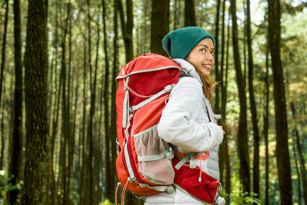 Lächelnde asiatische reisendfrau mit rucksack erforschen