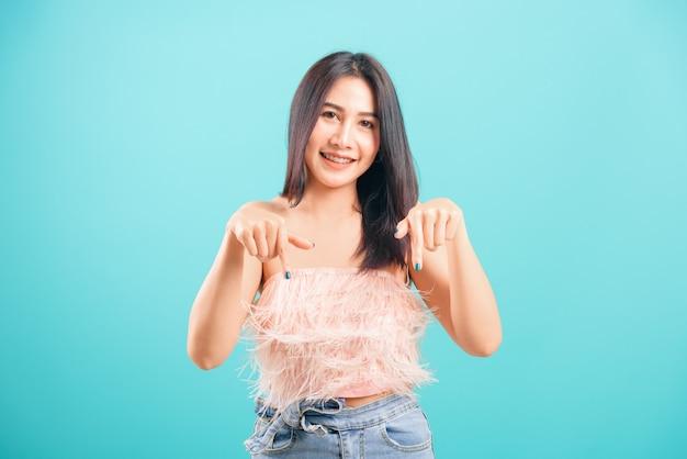 Lächelnde asiatische schöne frau, die finger nach unten zeigt