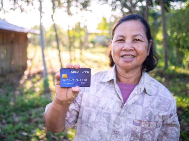 Lächelnde asiatische senoirfrau, die kreditkarte zeigt.