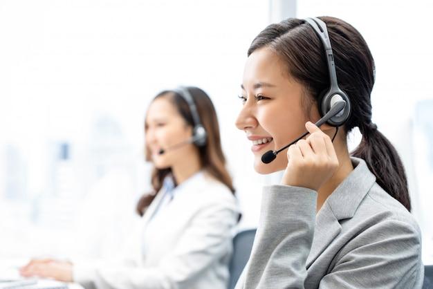 Lächelnde asiatische telemarketing-frau, die im call-center-büro arbeitet