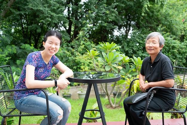 Lächelnde asiatische tochter und mutter auf stühlen mit tabelle am hinterhof