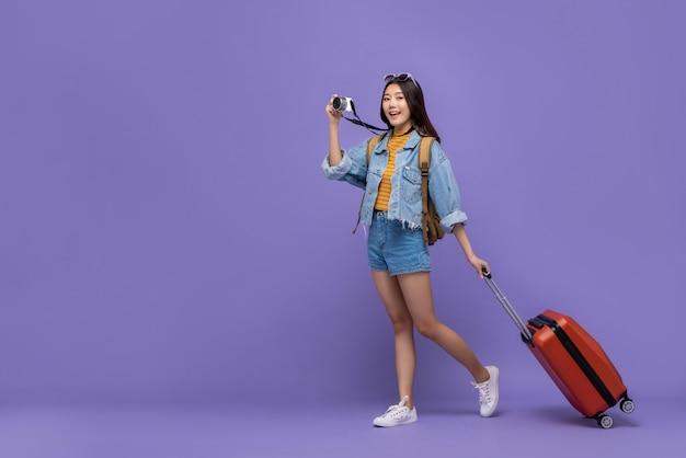 Lächelnde asiatische touristische frau mit kamera und gepäck