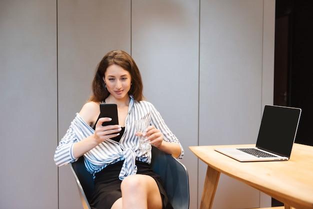Lächelnde atemberaubende frau mit braunen haaren, die bequem auf einem stuhl sitzt und ein persönliches smartphone verwendet using