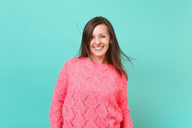 Lächelnde atemberaubende junge frau in gestricktem rosa pullover mit flatternden haaren einzeln auf blauem türkisfarbenem wandhintergrund, studioporträt. menschen aufrichtige emotionen, lifestyle-konzept. kopieren sie platz.