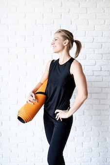 Lächelnde athletische frau in der schwarzen sportbekleidung auf weißem backsteinmauerhintergrund