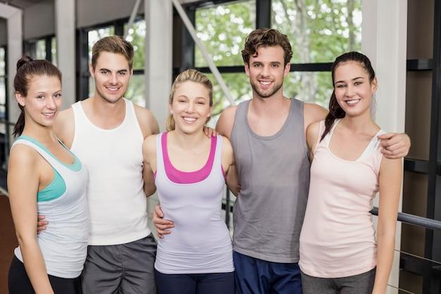 Lächelnde athletische freunde, die auf spur umarmen