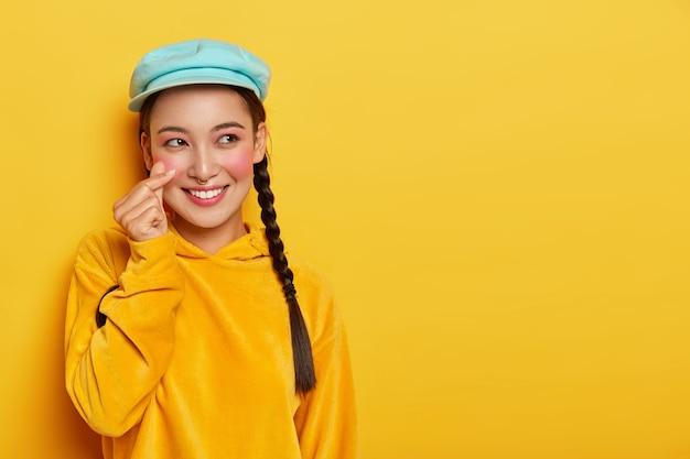 Lächelnde attraktive asain frau mit zöpfen, hat rote wangen, macht koreanisch wie zeichen, trägt baskenmütze und sweatshirt, hat verträumten gesichtsausdruck