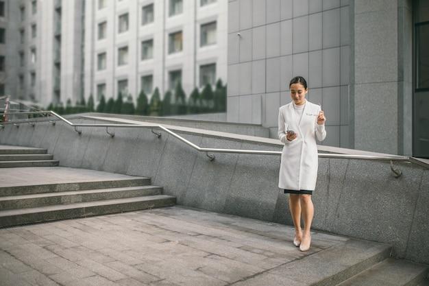 Lächelnde attraktive asiatische geschäftsfrau in gläsern liest eine zeitung, die sich auf den handlaufkollegen nahe bürozentrum m stützt