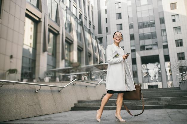 Lächelnde attraktive asiatische geschäftsfrau in gläsern mit einer zeitung trifft einen kollegen nahe bürozentrum
