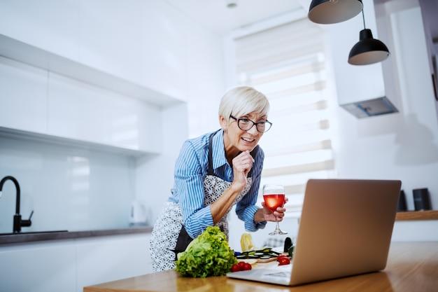 Lächelnde attraktive blonde ältere frau in der schürze, die laptop für rezept und wein trinken verwendet