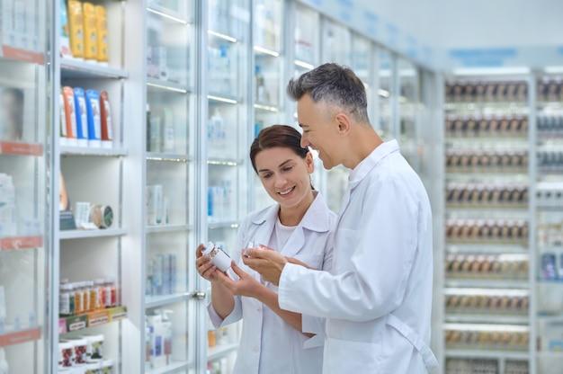 Lächelnde attraktive drogistin und ihr fröhlicher männlicher kollege, der medikamentenflaschen in den händen hält
