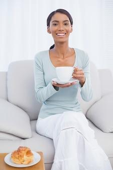 Lächelnde attraktive frau, die frühstückt