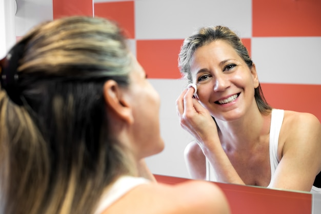 Lächelnde attraktive frau, die ihr make-up entfernt