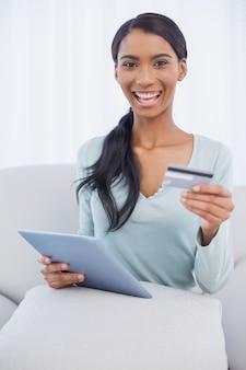 Lächelnde attraktive frau, die ihren tabletten-pc verwendet, um online zu kaufen