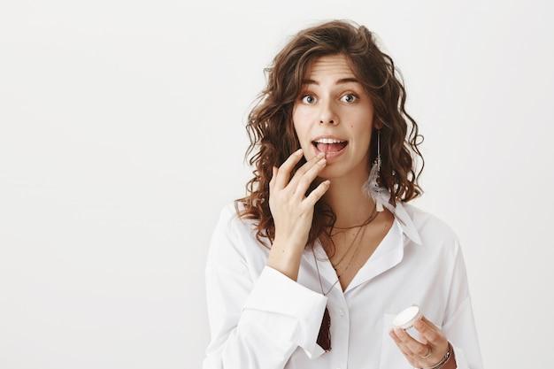 Lächelnde attraktive frau, die lippenbalsam anwendet
