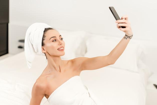 Lächelnde attraktive frau, die selfie auf dem bett im schlafzimmer nach dusche tut