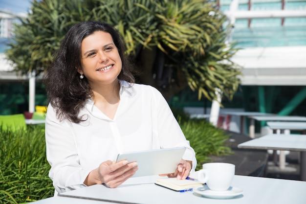 Lächelnde attraktive frau, die tablette im straßencafé bearbeitet und verwendet