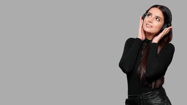Lächelnde attraktive frau in drahtlosen kopfhörern hören musik, lokalisiert auf grauem hintergrund