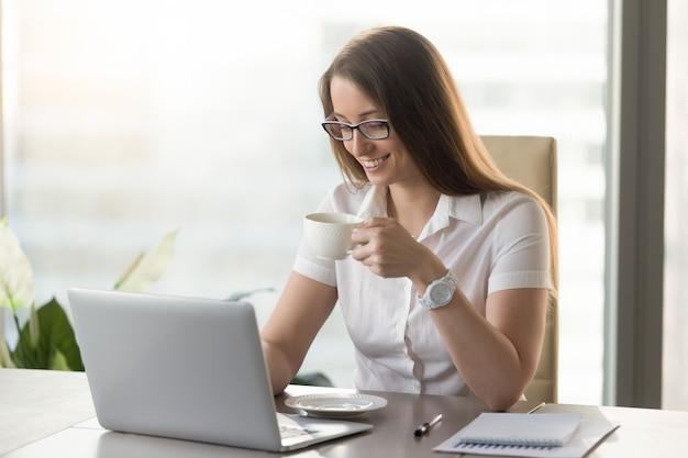 Lächelnde attraktive geschäftsfrau, die belebenden kaffee während des bruches am arbeitsplatz trinkt