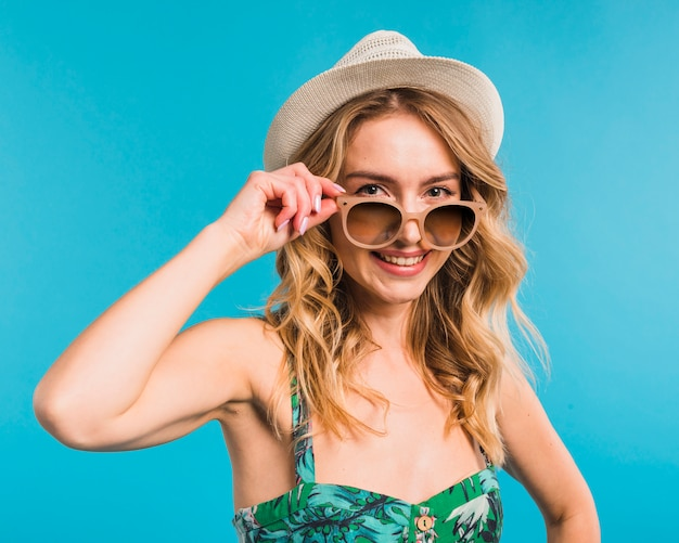 Lächelnde attraktive junge frau im hut und in der sonnenbrille