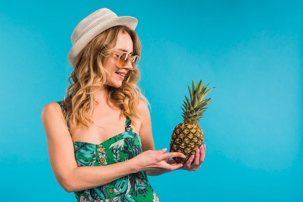 Lächelnde attraktive junge frau im kleid mit dem hut und sonnenbrille, die frische ananas betrachten
