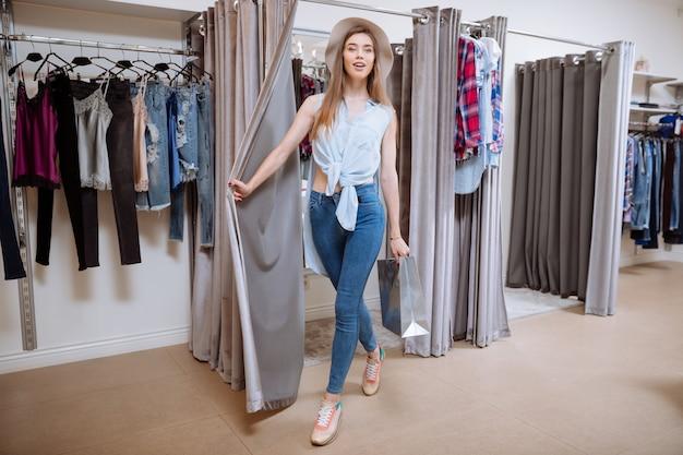 Lächelnde attraktive junge frau mit einkaufstasche, die aus der umkleidekabine geht