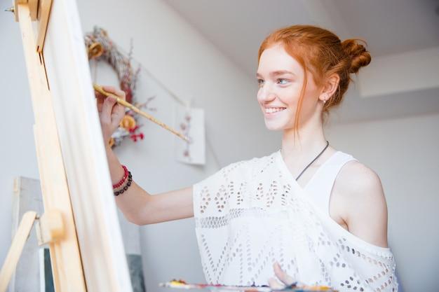 Lächelnde attraktive junge malerin mit roten haaren, die in der künstlerwerkstatt auf leinwand malen