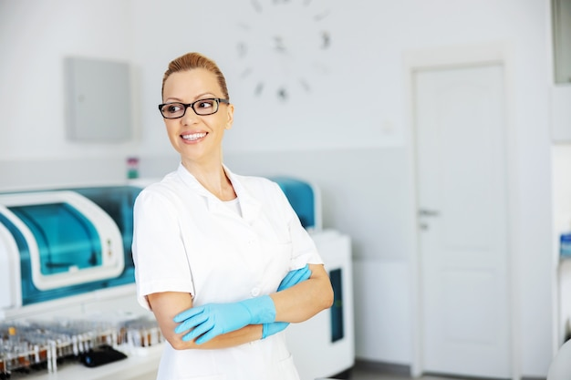 Lächelnde attraktive positive blonde laborassistentin in steriler uniform mit gummihandschuhen beim stehen im labor mit verschränkten armen und wegschauen.