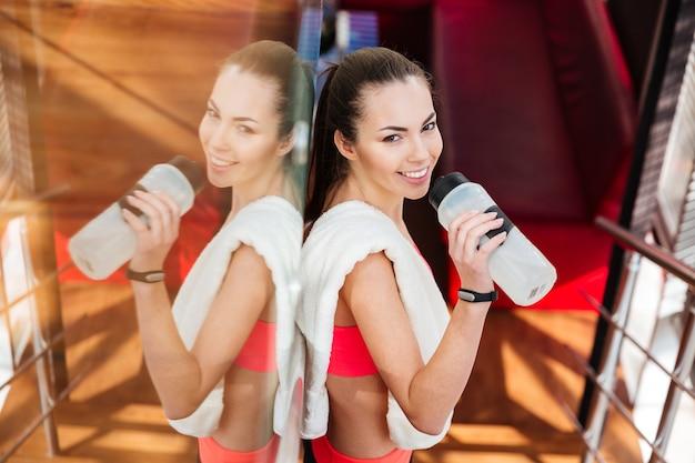 Lächelnde attraktive sportlerin, die nach dem training im fitnessstudio steht und wasser trinkt