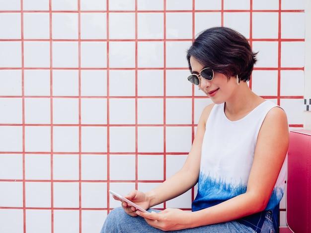 Lächelnde attraktive stilvolle asiatische frau mit kurzem haar, die weißes hemd und sonnenbrille trägt, die auf rotem sitz sitzt und smartphone auf weißem und rotem fliesenwandhintergrund mit kopienraum verwendet.