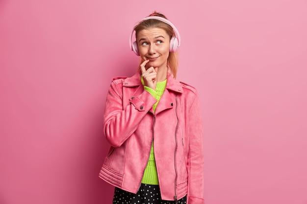 Lächelnde attraktive tausendjährige frau mit verträumtem ausdruck hört lieblingslied, trägt kopfhörer, genießt wiedergabeliste, trägt rosa jacke, steht drinnen. hobby, freizeit, lifestyle