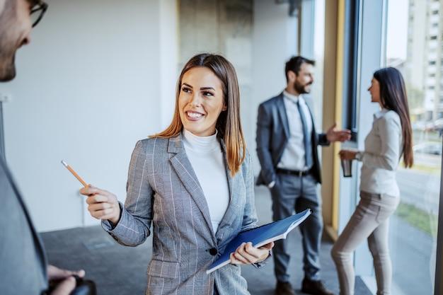 Lächelnde attraktive weibliche vorgesetzte, die mit ihrer mitarbeiterin über neue ideen für den bau ihrer erneuerung spricht. gebäude im innenraum des bauprozesses.