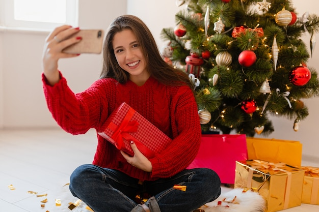 Lächelnde aufgeregte hübsche frau im roten pullover, der zu hause am weihnachtsbaum sitzt, der geschenke und geschenkboxen auspackt, die selfie-foto auf telefonkamera nehmen