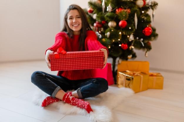 Lächelnde aufgeregte hübsche frau im roten pullover, der zu hause am weihnachtsbaum sitzt, der geschenke und geschenkboxen auspackt