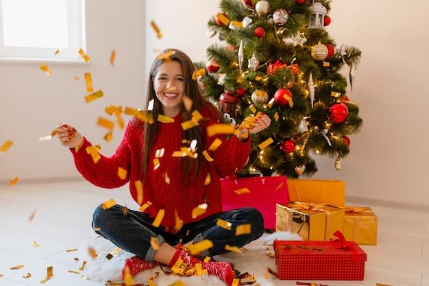 Lächelnde aufgeregte hübsche frau im roten pullover, der zu hause am weihnachtsbaum sitzt und goldenes konfetti wirft, umgeben von geschenken und geschenkboxen