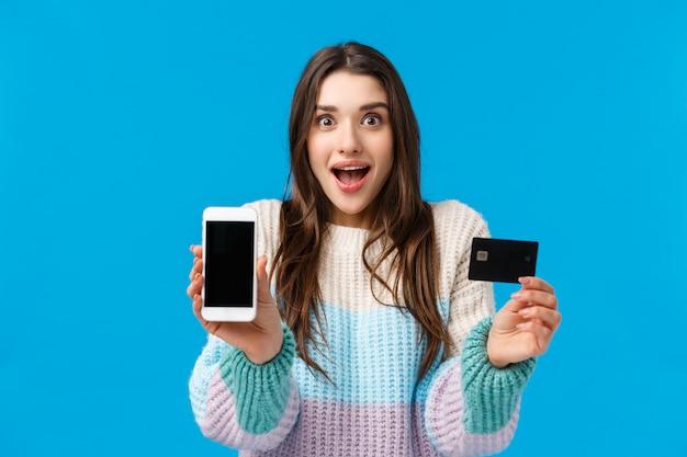Lächelnde, aufgeregte und faszinierte junge frau, die über coole neue app, bankanwendung, einzahlungs- oder rückzahlungsservice spricht und den smartphone hält, der anzeigenkamera gegenüberstellt, kreditkarte und grinst amüsiert