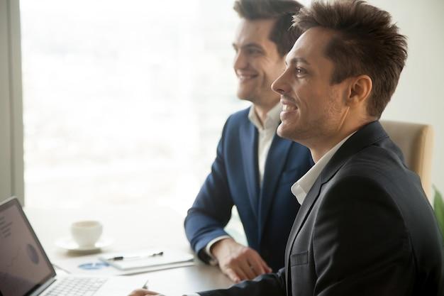 Lächelnde aufmerksame geschäftsmänner, die an der konferenzsitzung, seite teilnehmen
