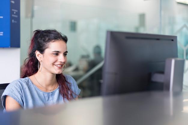 Lächelnde aufpassende mitteilungen der jungen frau auf bildschirm, in einem coworking raum.