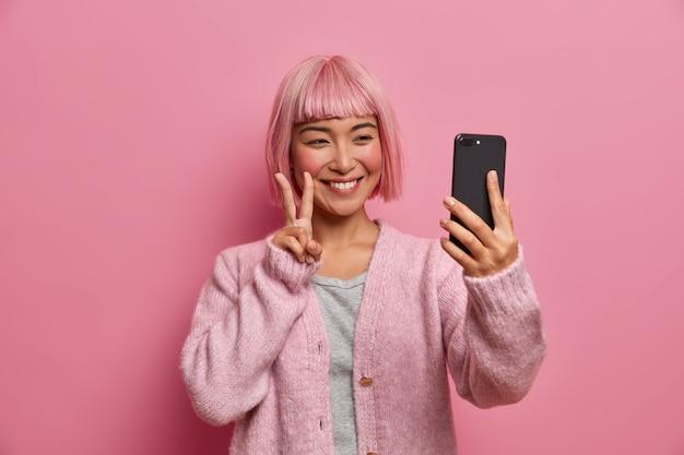 Lächelnde aufrichtige asiatische frau macht friedensgeste, begrüßt freund während der videokonferenz, macht selfie per smartphone, trägt einen lässigen pullover, hat trendig gefärbtes haar