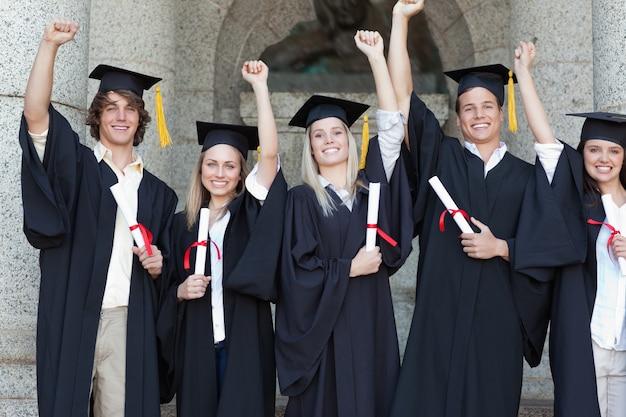 Lächelnde aufwerfende absolvent beim anheben der arme
