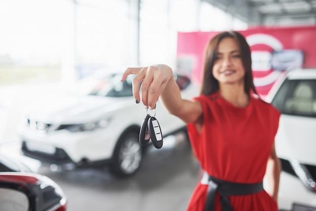 Lächelnde autoverkäuferin, die ihre neuwagenschlüssel, verkaufsstelle und verkaufskonzept überreicht. glückliche frau der käufer