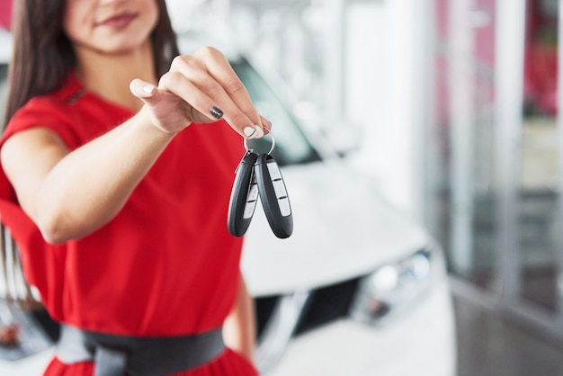 Lächelnde autoverkäuferin, die ihre neuwagenschlüssel, verkaufsstelle und verkaufskonzept überreicht.