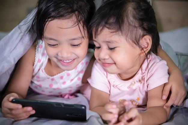Lächelnde babyschwestern genießen mit einem intelligenten telefon auf dem schlafzimmer