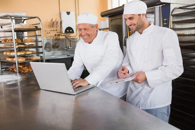 Lächelnde bäcker, die zusammen an laptop arbeiten