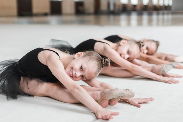 Lächelnde ballerinamädchen, die auf tanzboden aufwerfen