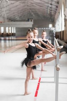 Lächelnde ballerinamädchen, die ihr bein auf bar ausdehnen