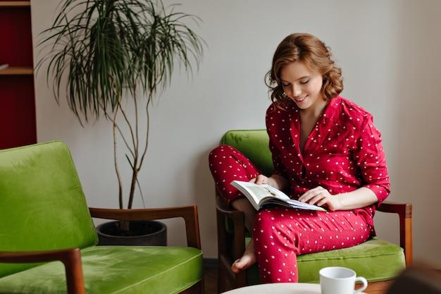 Lächelnde barfußdame, die buch liest. innenaufnahme der frau im roten pyjama, der im sessel kühlt.